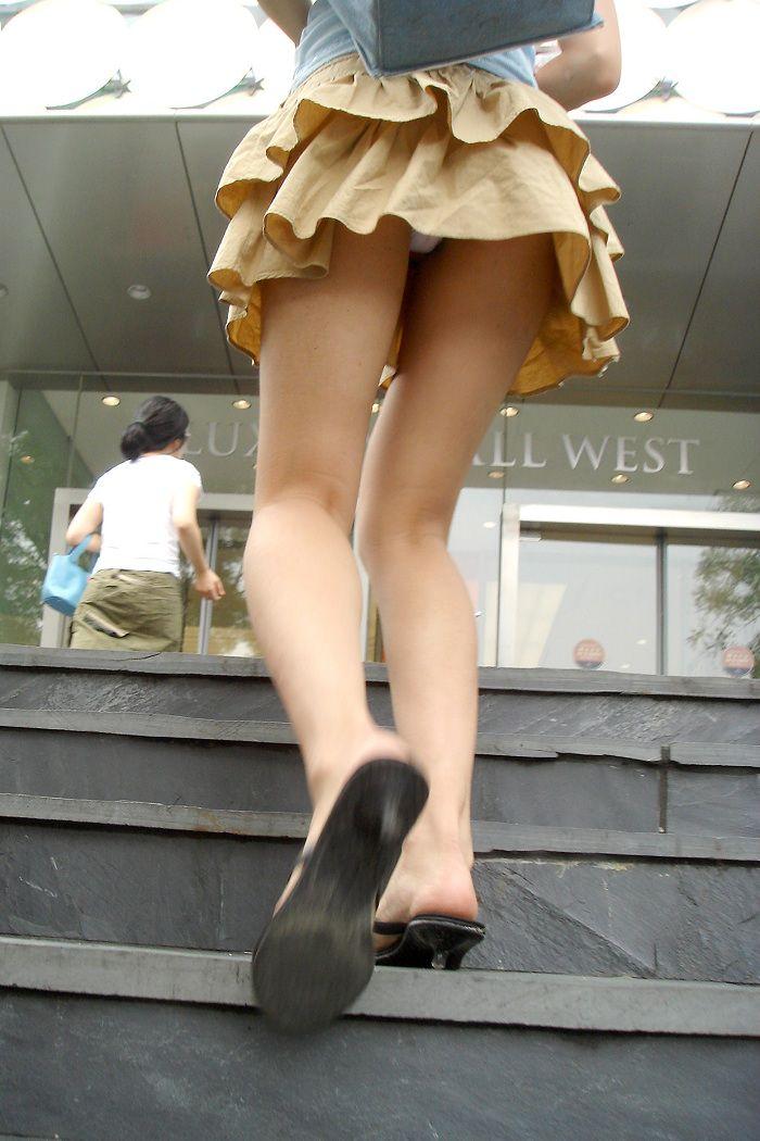 ヒラヒラしたスカートを履いた女を階段の下から撮影