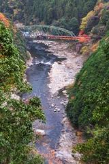 晩秋の保津川橋梁を渡るトロッコ列車