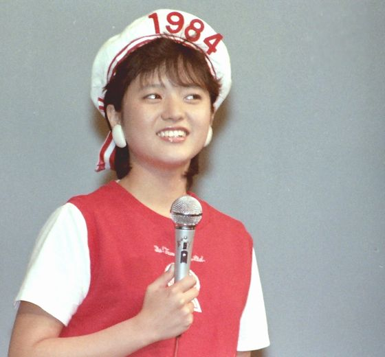 赤と白の衣装に身を包み、マイクを持つアイドル時代の三田寛子